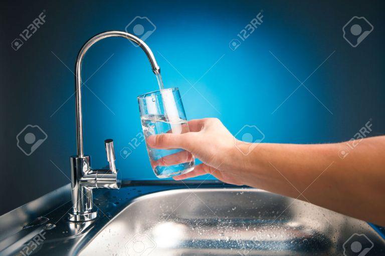 34237088-mano-versando-un-bicchiere-d-acqua-dal-rubinetto-filtro-archivio-fotografico